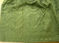 Detail quilted petticoat, England or North America, 1760-1780. Green silk quilted with floral motifs and zigzag design.