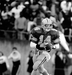 Black and white photo of University of Oregon quarterback Bill Musgrave scrambling with the football during a game played at Autzen Stadium in 1990. ©University of Oregon Libraries - Special Collections and University Archives