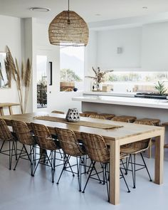 A tropical kitchen with sleek white cabinets, a wicker lampshade, rattan chairs, tropical plants and pampas grass. Dining Room Design, Dining Area, Tropical Kitchen, Rattan Dining Chairs, Furniture Chairs, Dining Table With Chairs, Kitchen Furniture, Tropical Dining Chairs, Furniture Stores