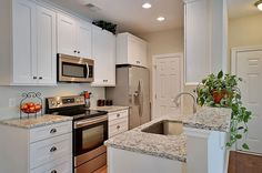 Small galley kitchen in traditional style with white cabinets and peninsula