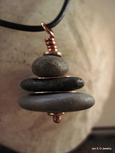 Beach stones gathered by me have been stacked and drilled to make this Om Rock cairn. Stacking stones is a way of finding balance and pointing one in the right direction. This cairn is two grayish rocks with a black rock in the middle. Copper spacers from bench scraps are between the rocks and the top and bottom of the cairn are brass spacers.