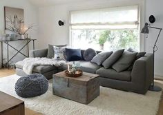 Grey sofa with wooden trunk as coffee table.