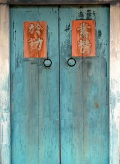 An entrance to an old farmhouse with lucky charm Chinese characters. The inscription reads, - May the God of the House Door bless this home with prosperity and riches -.