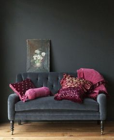Deep shade of slate, blue/grey velvet settee and walls, with warm, vibrant pinks and embroidered burgundy~