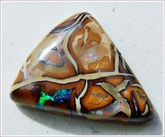 A beautiful & uniquely patterned Koroit Matrix Gem with a play of reds and brilliant gem greens!