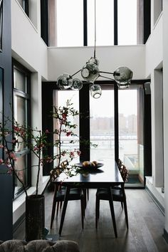 Dream dining room.  Beautiful, natural light flooding in in this gorgeous home. Home decor inspo with all white minimal and mod furniture. Pops of color through art, organic/florals, vintage pieces and accent furniture.   Read the inspo post here: http://becauseimaddicted.net/2013/04/a-peek-inside-athena-calderones.html?utm_source=feedly
