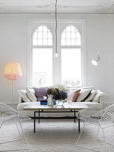 white swedish style living room with hanging bulb light and bertoia chairs