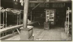"""The living conditions in the bunkhouse for George and Lennie were less than ideal. It was a long building with a small stove, and several bunks along the sides. For shelving they had apple crates and a small table in the center of the room for playing cards. I imagine it got cold in there during winter due to the quality of the bunkhouse. """"Inside, the walls were whitewashed and the floor unpainted... and in the fourth, a solid door with a wooden latch."""" Tupper Lake, The Bunkhouse, Small Stove, Lumber Mill, Square Windows, Apple Crates, Solid Doors, Wood Logs, Of Mice And Men"""