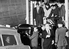 JFK's coffin is unloaded from Air Force One at Andrews Air Force Base, on Friday, 11/22/63.   Mrs. Kennedy watches, as Clint Hill (to the right) figures out how to help her make the nearly six foot jump to the ground.