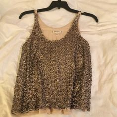 Gold sequined tank It fits loosely, but is a little short, especially if you have a larger chest. Will cause it to be shorter. Super cute top. I've worn a few times, for New Years. Comfortable, cute, and sexy! Decree Tops Tank Tops