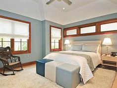 All-white Roman shades provide understated elegance and allow the blue bench to be the focal point in this bedroom.