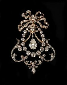 A Belle Epoque diamond brooch, circa 1910, designed  as an articulated swag, the central pear shaped diamond drop, weighing  2.08 carats