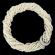 Twelve strands of lustrous light cream rose freshwater cultured pearls are clasped by a sparkling crescent