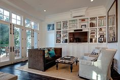 Simple and stylish living room design with built in shelving.  From a 4-story Craftsman style home construction by Lavallee Construction, discovered on Porch.com