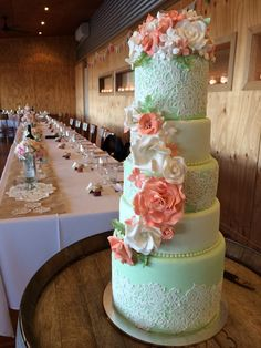 A five tiered wedding cake in mint greens creams and coral with edible pearls and edible lace
