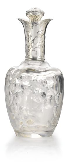 A FABERGÉ SILVER-MOUNTED GLASS DECANTER, MOSCOW, 1899-1908 the body moulded with a meandering trail of pebble-like forms, the neck and stopper cast with foliage within gnarled wood stems, struck K.Fabergé in Cyrillic beneath the Imperial Warrant, 84 standard.