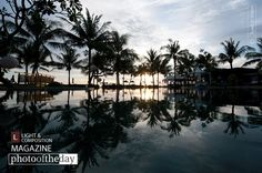 """Mirror Mirror, by Eyad Al Shami - """"This hotel pool was so still (since people left for the beautiful beach) that it was almost like a solid reflective surface. The se-metrical look and feel of the scene is what drives the attention to the beautiful surrounding trees, which makes it look like a desert oasis. The setting sun is what gave the final touch to such beautiful scene""""."""