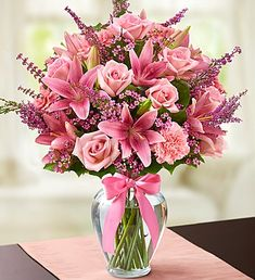 Expressions of Pink™ for Mother's Day- pink roses, lilies, carnations, waxflower and heather, accented with salal inside a clear glass vase with a stylish decorative ribbon $59.99- $79.99