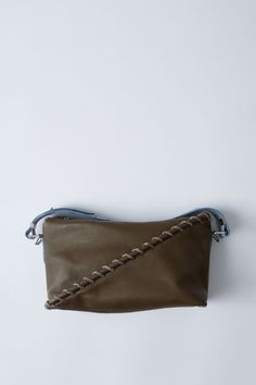 Acne Studios Rope Messenger oil green/light blue is a leather shoulder or cross body bag with large whipstitch details.
