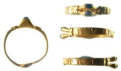 14th century, gold finger ring. The hoop is rectagular in shape and tapers towards its back, both ends of the hoop terminate in a pair of clasped hands. The outer face of the hoop has incised lettering in it and reads 'AVE MARIA.