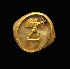 A GREEK GOLD AND GLASS RING BEZEL  Circa 4th-3rd Century B.C.  Composed of an oval plaque of transparent pale green glass over a gold foil cut-out of a winged Eros aiming his bow, on a short groundline; mounted as a ring in a modern gold setting