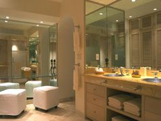 This bathroom features a vanity seating area with a floor-to-ceiling mirror and upholstered cube stools.