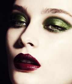 Green eye makeup, dark lips.