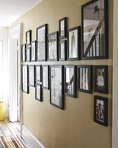 Mark a horizontal midline on the wall, and hang all pictures above or below it... brilliant!    Whoa - this is sort of brilliant.