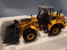 Die Cast New Holland W190B Wheeled Loader in 1:50 scale with Articulated steering from ROS. It is new in the original box. It is superbly painted throughout with the yellow and gray New Holland color scheme and has vibrant graphics and lettering.  It is made in Italy by ROS.  A great construction vehicle.