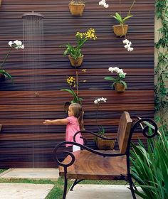 A paisagista Irene Cisneros teve uma boa sacada neste jardim de 18 m²: criou um painel vertical com ripas de madeira e, ali, pregou vasos com orquídeas falenópsis e chuva-de-ouro
