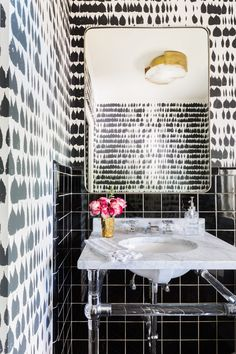 Feminine powder room with printed black and white wallpaper, a mounted silver mirror, a sink with a marble top with pink flowers
