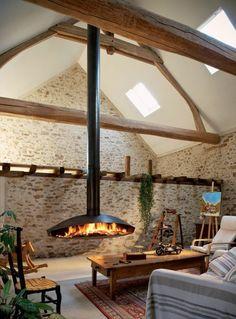 moderne kaminöfen hängender kamin wohnzimmer steinwand teppich pflanzen