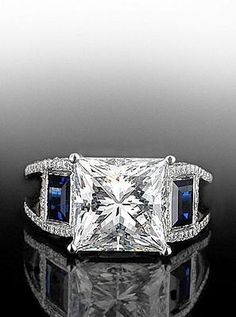 Princess center diamond with two quadrillion sapphires in a split shank mounting. By Bez Ambar. Available at Alson Jewelers.