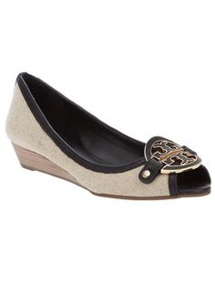 White cotton 'Demi' shoe from Tory Burch featuring a peep toe, shallow wedge heel and black and gold tone front logo plaque.