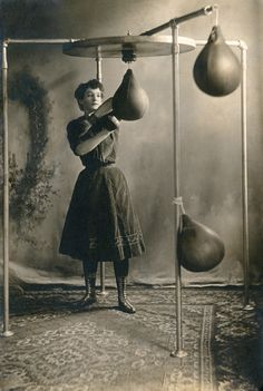 A young woman working out with boxing gloves and a punching bag, 1890.