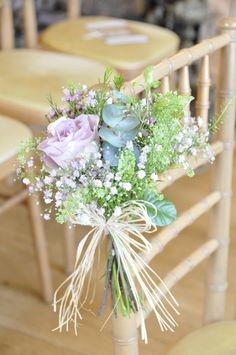small bunches tied onto chairs are an affordable way to dress the aisle  www.inspirationweddingflowers.com