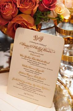 An ornate menu features the couple's monogram in gold on off-white paper.