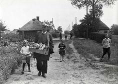Een marskramer met zijn kist met koopwaar loopt door het gehucht Heike. Een drietal kinderen loopt met hem op. Heike, Noord-Brabant, 1936.
