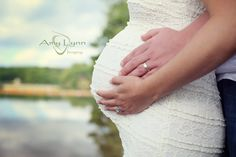 Maternity Photo with Close-up of Wedding Rings and Baby Bump in White Dress