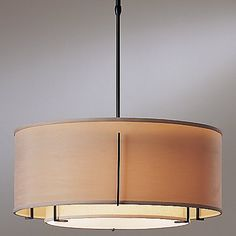 The Hubbardton Forge Exos Double Shade Suspension- Medium enhances the appeal of your interiors by its sophisticated looks while shimmering a heartwarming radiance. The Exos Double Shade Suspension- Medium features outer fabric shade, Natural Linen inner fabric shade and hand-forged wrought iron body.