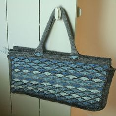 This knitting bag is made in Tunisian crochet, a wave stitch alternated with a basic stitch. The waves seemed appropriate for the blues and grays I used and the Tunisian crochet makes for a sturdy bag.