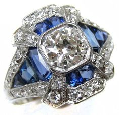 Art Deco sapphire and diamond ring, circa 1910. It is millegrain set with a cushion cut diamond, the surrounding calibre cut sapphires forming a lozenge, diamond dart highlights to the corners and a diamond set outer border. Via Diamonds in the Library.