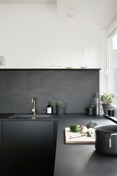 Purely utilitarian surfaces, like concrete kitchen countertops. The material is eco-friendly and affordable, and when painted or sealed in a sleek color, like the matte charcoal counters featured in this kitchen, the look feels fresh yet approachable. Black Kitchens, Home Kitchens, Kitchen Black, Narrow Kitchen, Charcoal Kitchen, Cottage Kitchens, Modern Kitchens, Kitchen Interior, New Kitchen