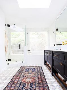 white bath with moroccan tiles and black fixtures and vanity // amber interiors