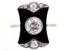 A very stylish Art Deco ring set with a shaped onyx plaque with a large 65 point old mine cut diamond in the centre. The top and bottom are set with an old mine cut diamond and two rose diamonds in each part. It was made circa 1920-1930.