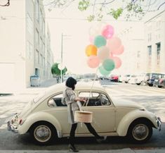 Model with balloons by a cute  vintage car