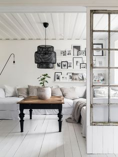 Painted floor, gallery wall, black framed door, white walls, natural wood to warm the room