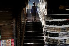SILHOUETTED ON A STAIRCASE: A man walked down a staircase in an alleyway in New Delhi on Tuesday. (Kevin Frayer/Associated Press)