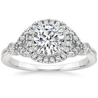 In this vintage-inspired engagement ring, a bezel-set center gem floats above a halo of diamond accents bordered by an octagonal frame. Bezel-set baguette accents create a look of shimmering beauty.