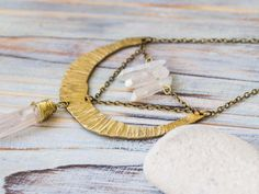 Irregular shaped unusual half moon pendant full of charm and wild character of raw uncut crystal. Tender glow of raw crystal overflow with beauty and magic and complement texture of brass crescent. Perfect present for crystal lover or yoga friend. It is more than just a pretty thing, it it a real talisman packed with good vibes! This long chain crescent pendant is created with bare solid brass cut by hand and hammered. Pendant includes real aura quartz points, uncut and unpolished, just…